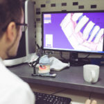 male dentist looking at intraoral scans of a patient's teeth