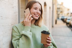 young woman smiling while talking on the phone and holding a coffee cup outdoors